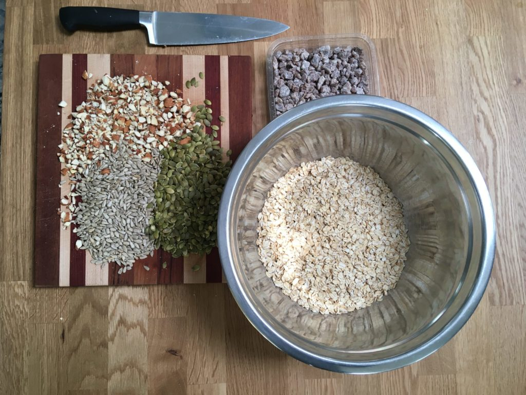 mixing bowl of muesli next to cutting board with chopped nuts