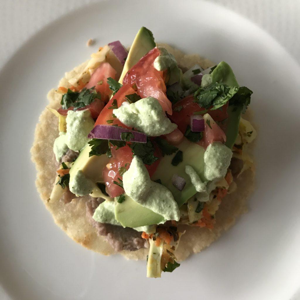 tostada topped with refried beans, slaw, salsa, avocados and cilantro crema