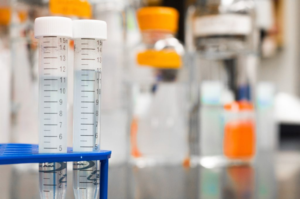 two test tubes in foreground with lab supplies and beakers in the background