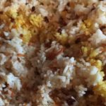 close-up of Persian-style rice: white rice with barberries and shredded carrot, with a drizzle of saffron-infused water turning some rice grains golden