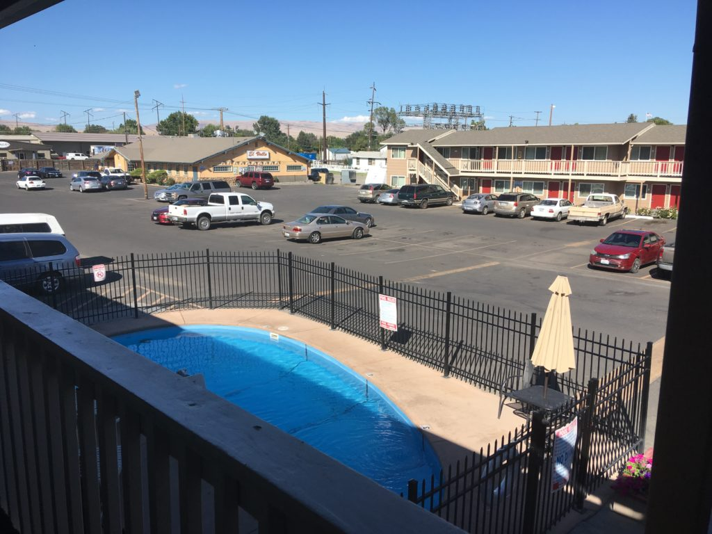 View outside the motel room I stayed in. A small pool in the foreground surrounded by a black metal gate. A large parking lot with another motel building and a Mexican restaurant in the background.