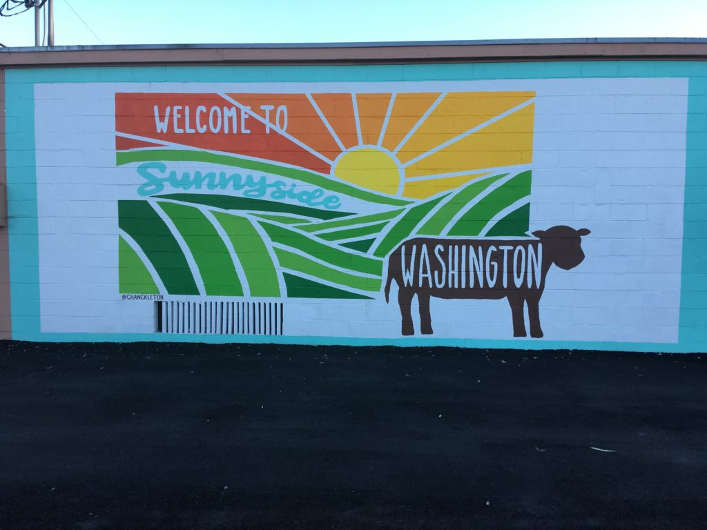 """Mural painted on the side of a building, showing green rolling pastures, a sunny sky, a silhouette of a cow, and the words, """"Welcome to Sunnyside Washington."""""""