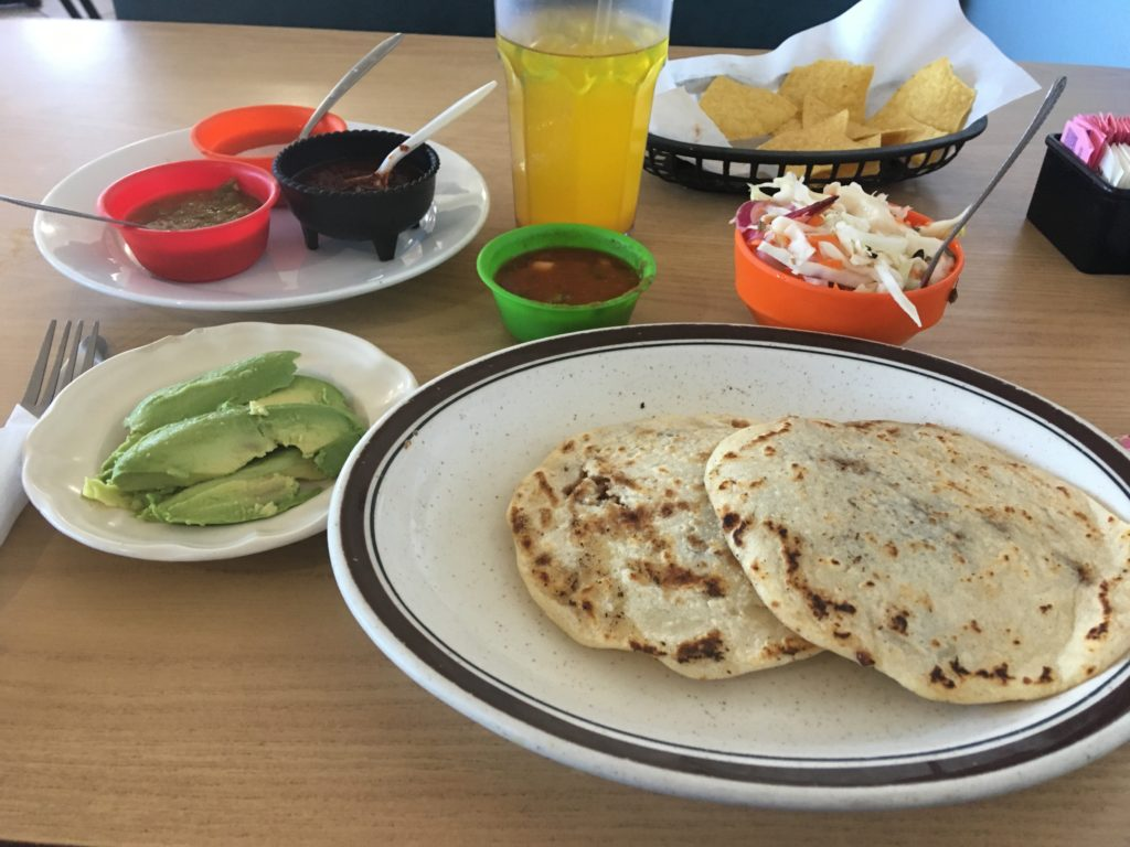 Freshly-made bean-filled pupusas, sliced avocados, 3 different moles, chips and salsa, cabbage slaw, and pineapple agua fresca.