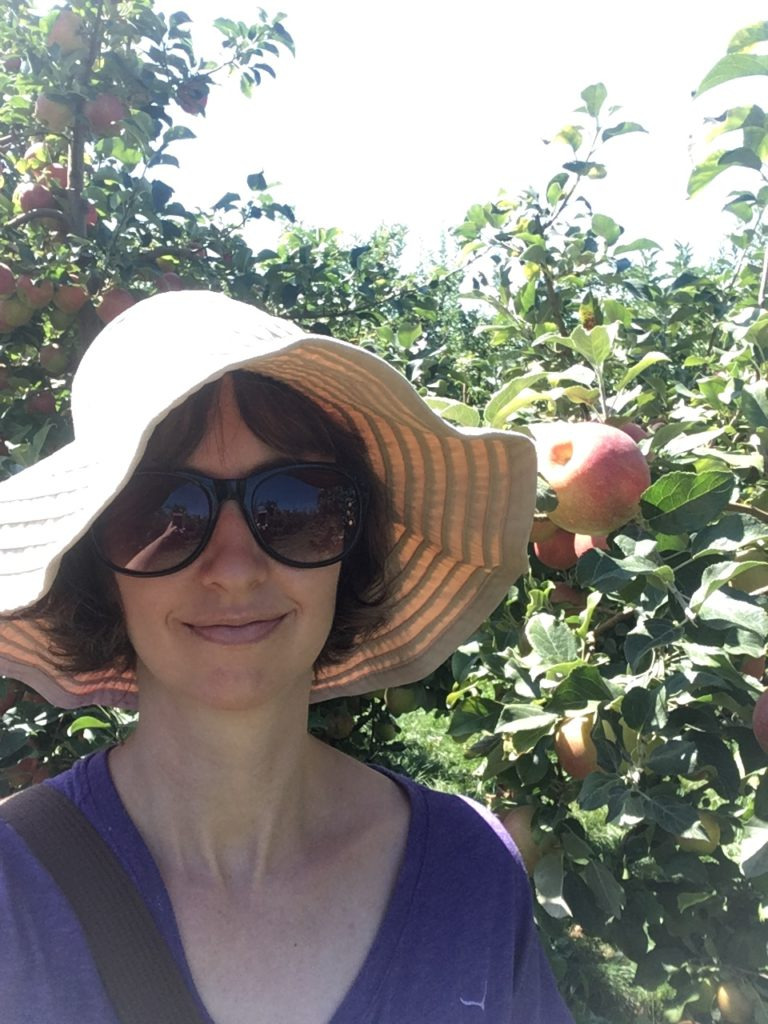 The author in a big floppy sun hat in sunglasses, surrounded by apple trees