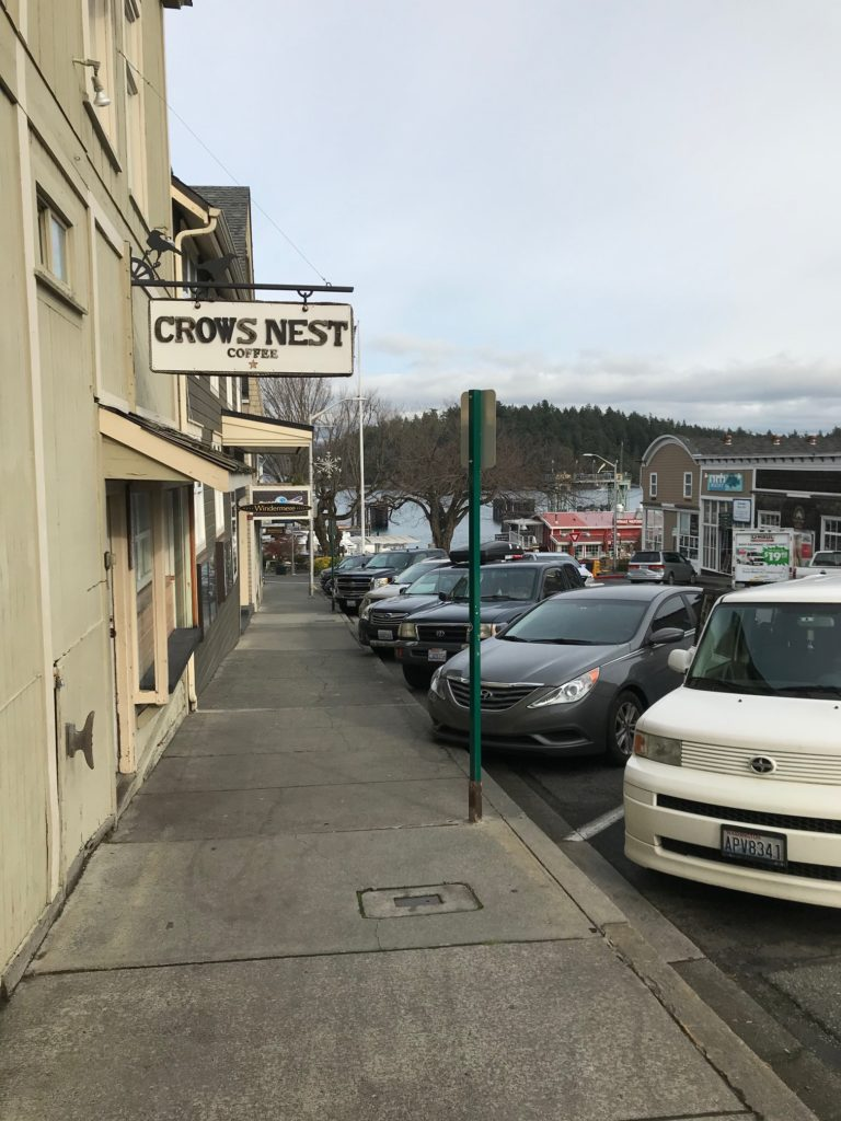 """line of shops with the ferry dock in the distance. Sign reads, """"Crows Nest coffee"""""""