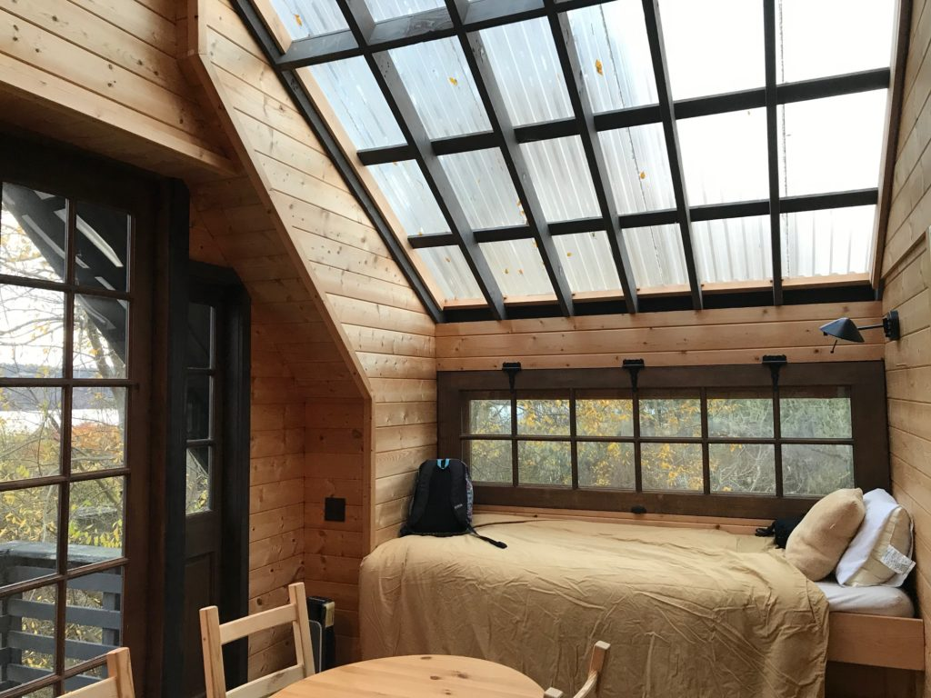 a little bed beneath a sloping skylight