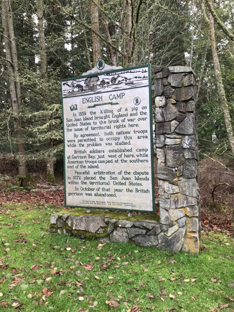 """Sign reads, """"English Camp. In 1859 the killing of a pig on San Juan Island brough England and the United States to the brink of war over the issue of territorial rights here. By agreement, both nations' troops were permitted to occupy this area while the problem was studied. British soldiers established camp at Garrison Bay, just west of here, while American troops camped at the southern end of the island. Peaceful arbitration of the dispute in 1872 placed the San Juan Islands within the territorial United States. In October of that year the British garrison was abandoned."""""""